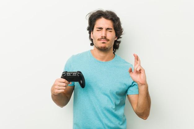 Junger mann, der einen gamecontroller kreuzt finger für das haben des glücks hält