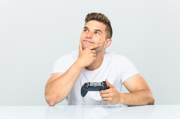Junger mann, der einen gamecontroller seitlich schaut mit zweifelhaftem und skeptischem ausdruck hält.