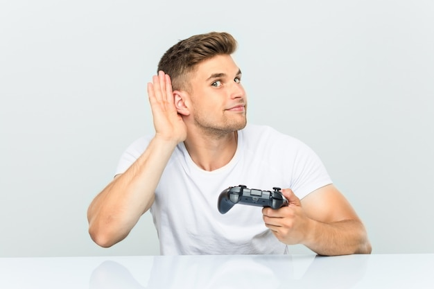 Junger mann, der einen gamecontroller versucht, einen klatsch zu hören hält.