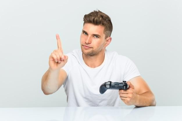 Junger mann, der einen gamecontroller zeigt nummer eins mit dem finger hält.