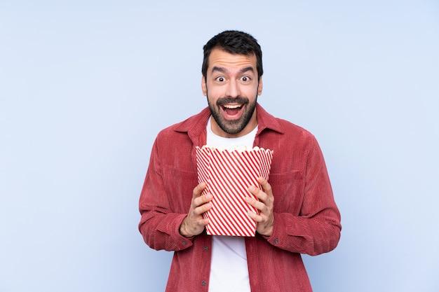 Junger mann, der einen großen eimer popcorn hält