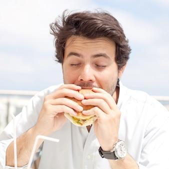 Junger mann, der einen hamburger isst