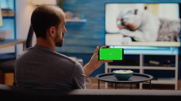 Junger mann, der einen horizontalen grünen bildschirm auf dem smartphone beobachtet