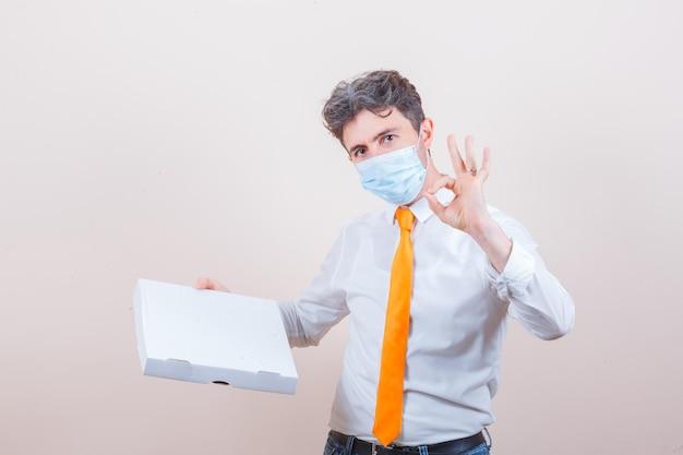 Junger mann, der einen karton hält und ein ok-zeichen in hemd, jeans, maske zeigt showing