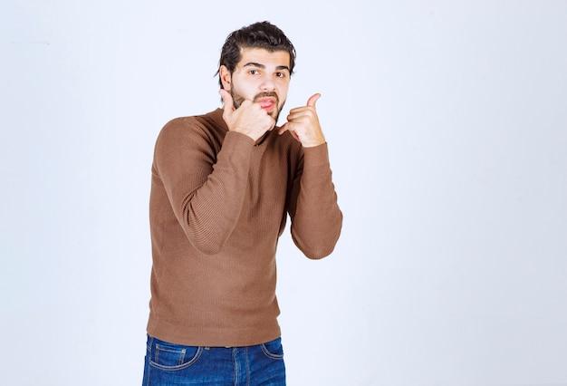 Junger mann, der einen lässigen pullover trägt, der über isoliertem weißem hintergrund steht und über die telefongeste spricht. foto in hoher qualität