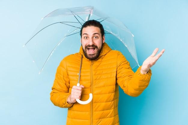 Junger mann, der einen langen haarblick hält, der einen regenschirm isoliert hält, der eine angenehme überraschung empfängt, aufgeregt und hände hebt.