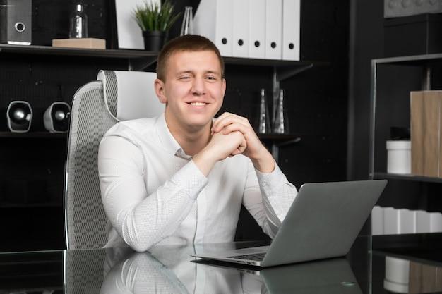 Junger mann, der einen laptop im büro bearbeitet