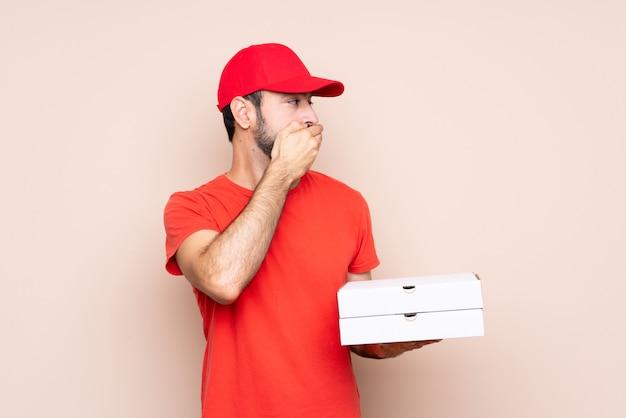 Junger mann, der einen pizzabedeckungsmund hält und zur seite schaut