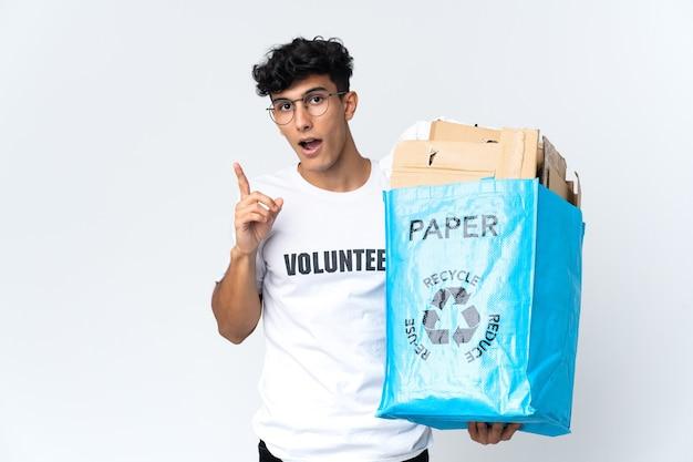 Junger mann, der einen recyclingbeutel voll papier hält, der beabsichtigt, die lösung zu realisieren, während er einen finger anhebt