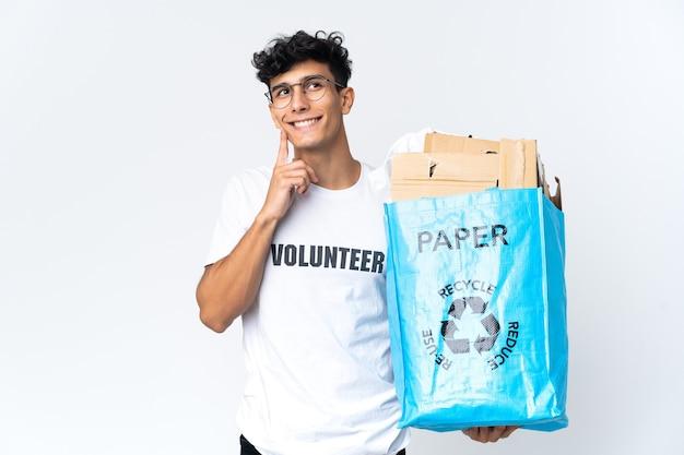 Junger mann, der einen recyclingbeutel voll papier hält, der eine idee denkt, während er aufschaut