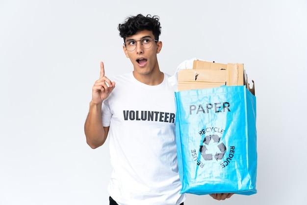 Junger mann, der einen recyclingbeutel voll papier hält und eine idee denkt, die den finger nach oben zeigt