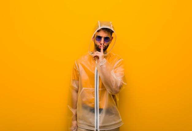 Junger mann, der einen regenmantel hält ein geheimnis oder bittet um ruhe trägt