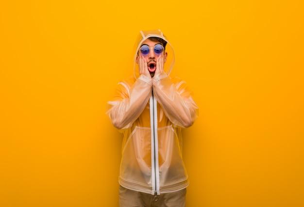 Junger mann, der einen regenmantel überrascht und entsetzt trägt