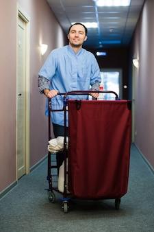 Junger mann, der einen reinigungswagen in einem hotel schiebt
