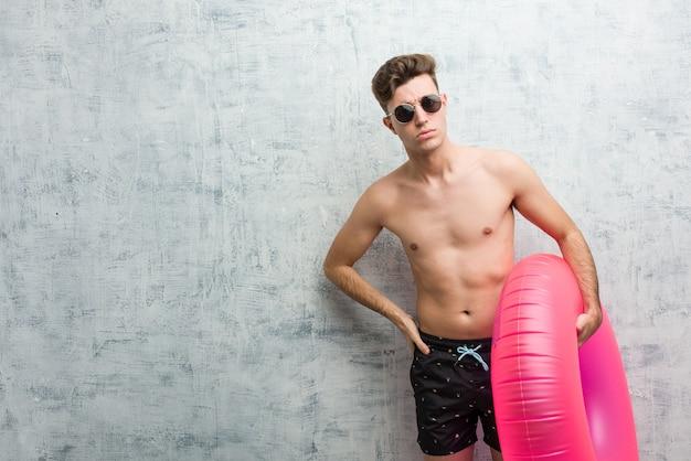 Junger mann, der einen rosa aufblasbaren donut hält, der einen badeanzug trägt, der jemanden sehr wütend schimpft.