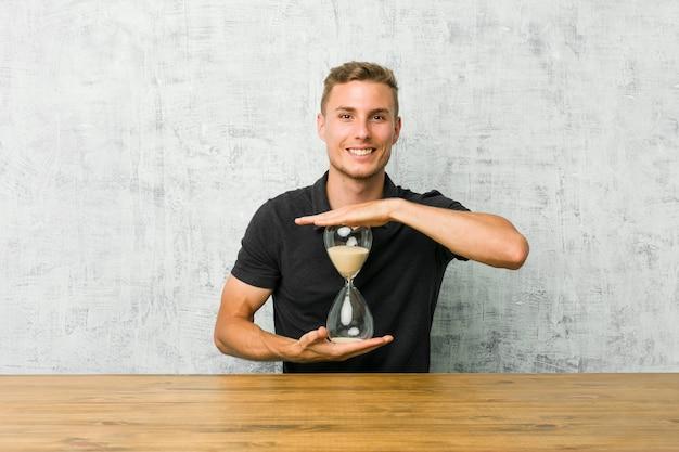 Junger mann, der einen sandtimer auf einer tabelle hält etwas mit beiden händen, produktdarstellung hält.