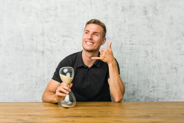 Junger mann, der einen sandtimer auf einer tabelle zeigt eine handyanrufgeste mit den fingern hält.