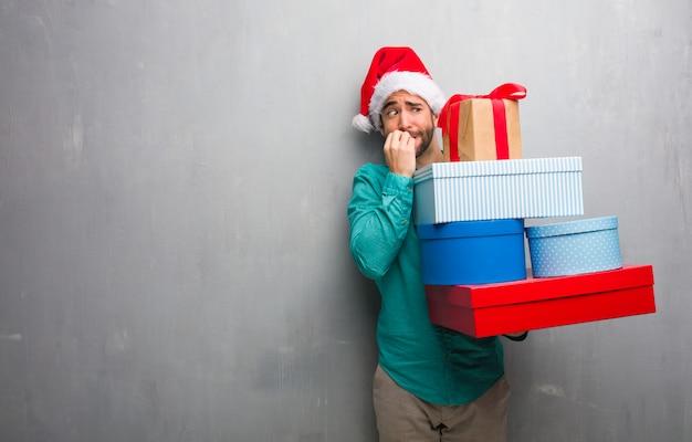 Junger mann, der einen sankt-hut hält geschenke beißend nägeln, nervös und sehr besorgt trägt