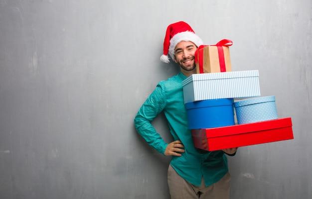 Junger mann, der einen sankt-hut hält geschenke mit den händen auf hüften trägt