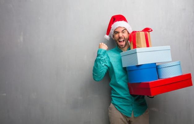 Junger mann, der einen sankt-hut hält geschenke überrascht und entsetzt trägt