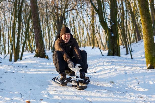 Junger mann, der einen schneeroller reitet