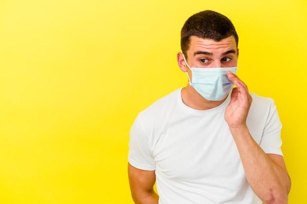 Junger mann, der einen schutz für coronavirus trägt, der auf gelber wand isoliert wird, sagt eine geheime heiße bremsnachricht und schaut zur seite