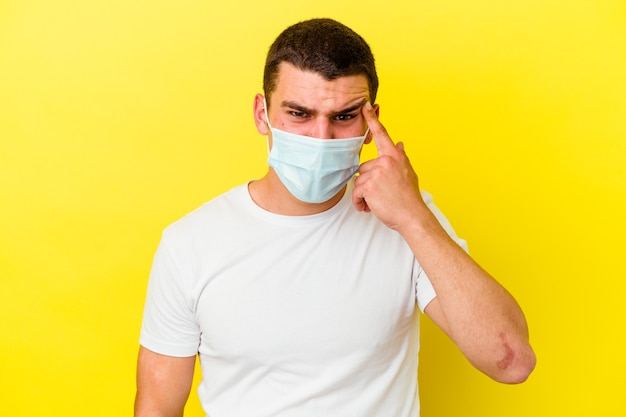 Junger mann, der einen schutz für coronavirus trägt, isoliert auf gelber wand, die eine enttäuschungsgeste mit zeigefinger zeigt