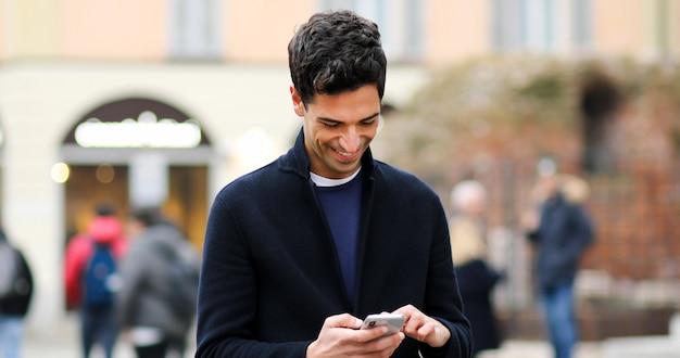 Junger mann, der einen smartphone im freien verwendet
