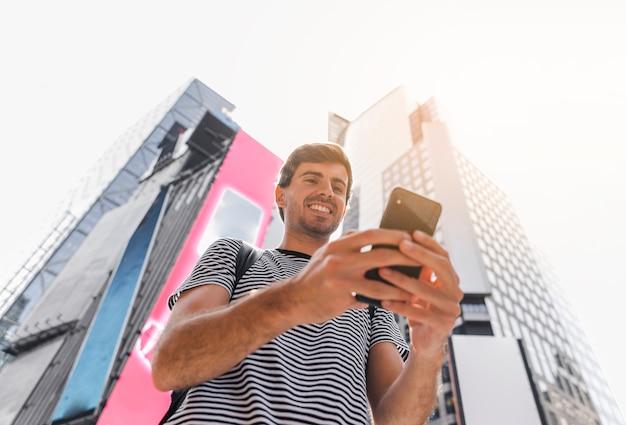 Junger mann, der einen smartphone mit beiden händen hält