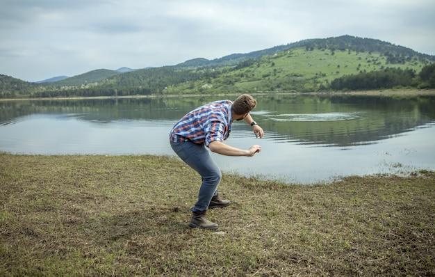 Junger mann, der einen stein auf seewasser überspringt
