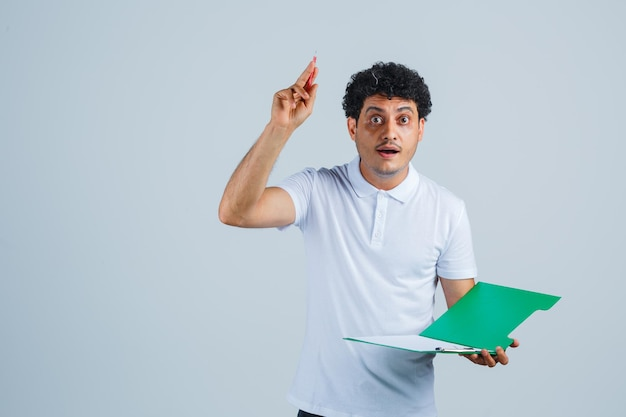Junger mann, der einen stift in der heureka-geste anhebt und ein notizbuch in weißem t-shirt und jeans hält und vernünftig aussieht. vorderansicht.