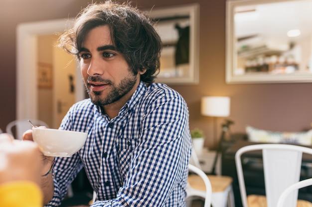 Junger mann, der einen tee am café mit seiner freundin trinkt.