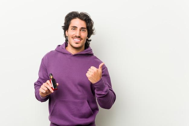 Junger mann, der einen vaporizer hält, der lächelt und beiseite zeigt und etwas an der leeren stelle zeigt.