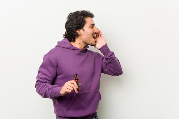 Junger mann, der einen vaporizer hält, der schreit und handfläche nahe offenem mund hält.