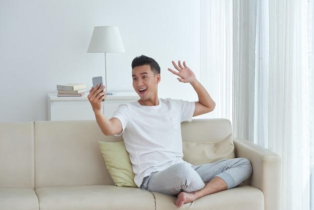 Junger mann, der einen videoanruf sitzt auf dem sofa in seinem wohnzimmer und eine grußwellengeste gibt macht