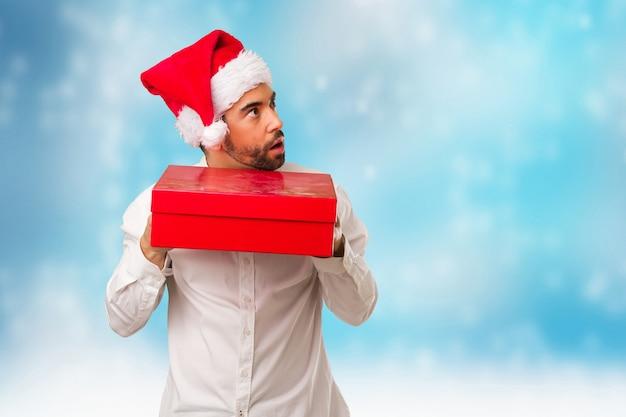 Junger mann, der einen weihnachtsmann-hut am weihnachtstag trägt