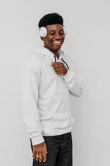 Junger mann, der einen weißen kapuzenpulli trägt