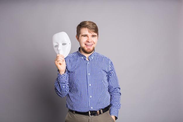 Junger mann, der einfache weiße maske abhebt, die gesicht, graue wand enthüllt