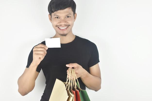 Junger mann, der einkaufstasche mit leerer karte hält konsumismus-shopping-lifestyle-konzept