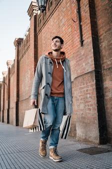Junger mann, der einkaufstaschen beim gehen auf die straße hält.