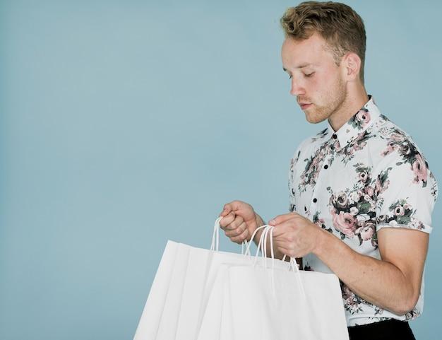 Junger mann, der einkaufstaschen betrachtet