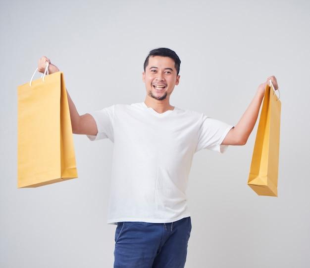 Junger mann, der einkaufstaschen hält.
