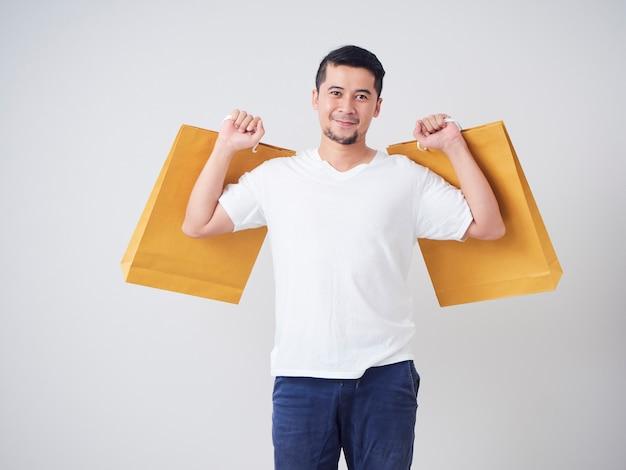 Junger mann, der einkaufstaschen trägt