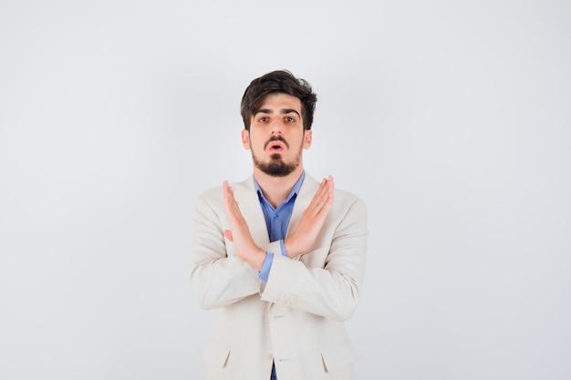 Junger mann, der einschränkung oder x-geste in blauem t-shirt und weißer anzugjacke zeigt und ernst aussieht