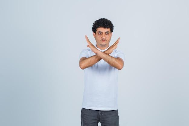 Junger mann, der einschränkung oder x-geste in weißem t-shirt und jeans zeigt und ernst aussieht. vorderansicht.