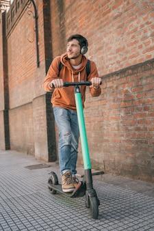 Junger mann, der elektrischen roller fährt.