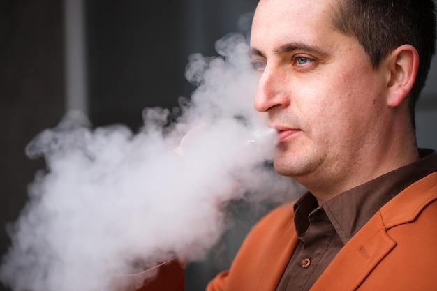 Junger mann, der elektronische zigarette raucht
