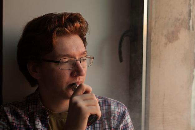 Junger mann, der elektronische zigarette raucht.