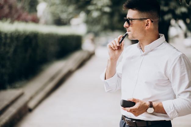 Junger mann, der elektrozigarette draußen im park raucht