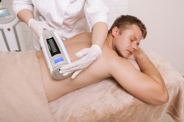 Junger mann, der endosphärenmassage an der schönheitsklinik erhält